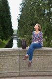 Beautiful girl sits on an old stone bridge Stock Images