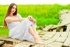 Beautiful girl sits on an old wooden bridge Royalty Free Stock Photo