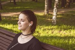 Beautiful girl sits on a park bench with closed eyes and listens to music on headphones royalty free stock photos