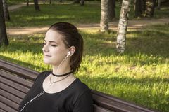 Beautiful girl sits on a park bench with closed eyes and listens to music on headphones stock image