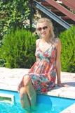 Beautiful girl sits on pool edge Stock Photos