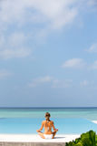 Beautiful girl sits in a pose of a lotus and meditates on the coast Maldives Stock Photos