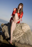 Beautiful girl sits on a rock Royalty Free Stock Image