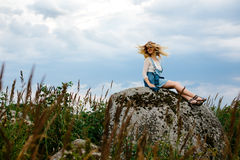 Beautiful girl sits on a rock Stock Images