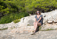 Beautiful girl sits on a rock in a forest Stock Image