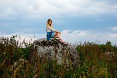 Beautiful girl sits on a rock Royalty Free Stock Photo