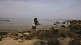 Beautiful girl sits on rocks near sea shore and looks into distance. stock video