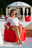 Beautiful girl sits on a soft red pufe Stock Photo