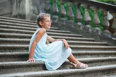 Beautiful girl sits on on the stairs in a park Royalty Free Stock Image