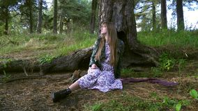 A beautiful girl sits under a large tree. The girl was lost. A beautiful girl sits under a large tree. The girl was lost stock video