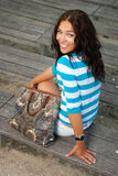 Beautiful girl sits on wooden bench Stock Image