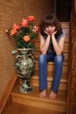 Beautiful girl sits on a wooden stair Royalty Free Stock Photography