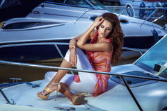 Beautiful girl sittin on the yacht. Photo of amzing brunette woman sitting on the yacht at evening Royalty Free Stock Photos