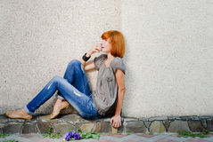Beautiful girl sitting against wall and looking up Stock Photos
