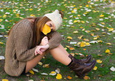 Beautiful girl sitting among autumn leaves and peeking behind or Royalty Free Stock Photos