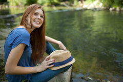 Beautiful girl sitting on the bank of the river Stock Photo