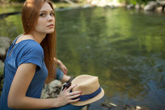 Beautiful girl sitting on the bank of the river Royalty Free Stock Photography