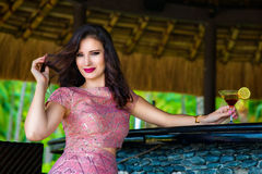 Beautiful girl sitting at the bar of the hotel on a tropical isl Royalty Free Stock Images