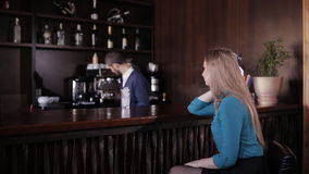 Beautiful girl sitting at the bar waiting for a cocktail, which prepares lovely bartender stock footage