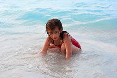 Beautiful girl sitting in the beach. Beautiful caucasian girl sitting in the beach with a mischievous look Royalty Free Stock Photography
