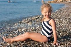 Beautiful girl sitting on the beach. At the seashore Royalty Free Stock Photo