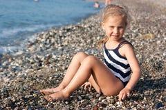Beautiful girl sitting on the beach. At the seashore Stock Photo