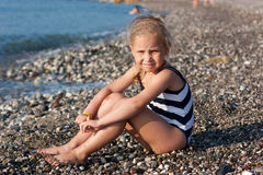Beautiful girl sitting on the beach. At the seashore Royalty Free Stock Image