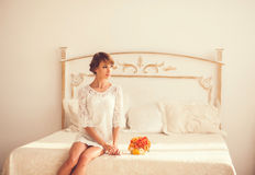 Beautiful girl sitting on a bed stock photography