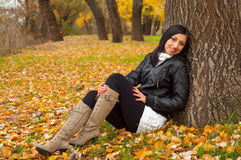 Beautiful girl sitting on the bed of leaves Stock Image