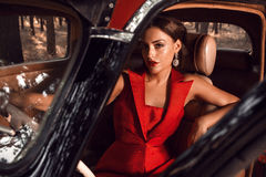 Beautiful girl sitting behind the wheel of vintage cars Stock Images
