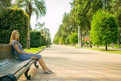 Beautiful girl sitting on the bench, the brown-haired woman in the striped dress, the trendy life style with your phone. A Sunny day in the Park Batumi Royalty Free Stock Images