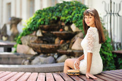 Beautiful girl sitting on a bench near a copyspace Royalty Free Stock Images