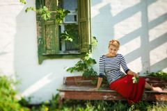 Beautiful girl sitting on bench near rural house Royalty Free Stock Images