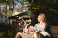 Beautiful girl is sitting on the bench in the park and enjoying with her dog Cavalier King Charles Spaniel Stock Photos
