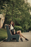 Beautiful girl sitting on bench in park Royalty Free Stock Photography