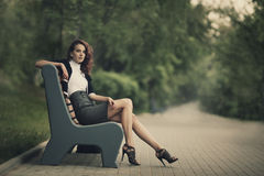 Beautiful girl sitting on bench in park Royalty Free Stock Images