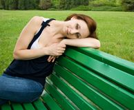 Beautiful girl sitting on a bench and sad Royalty Free Stock Image