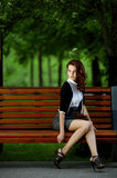 Beautiful girl sitting on bench Stock Photos