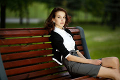 Beautiful girl sitting on bench Stock Image