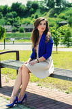 Beautiful girl sitting on bench. Young beautiful girl sitting on bench Stock Photo