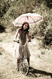 Beautiful girl sitting on bike. Beautiful girl sitting on bike and tree at rest in forest. Photo in retro style Stock Images