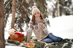 Beautiful,happy,cute,nice,smiling girl sit on warm,green blanket in the winter forest,drink hot tea,coffee,has wonderful picnic Stock Photography
