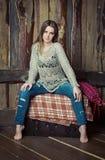 Beautiful girl sitting on the box. Beautiful girl sitting on the  rug covered box Royalty Free Stock Photography