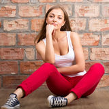 Beautiful girl sitting on a brick wall Stock Photography