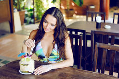Beautiful girl sitting in a cafe with coconut cocktail Stock Photos