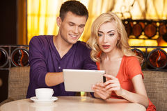 Beautiful girl sitting in cafe surprised. Handsome guy smiling and showing on screen Stock Image