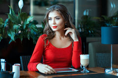 Beautiful girl is sitting in the cafe and thought. Stock Photos