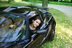 The beautiful girl is sitting in the car Stock Photos