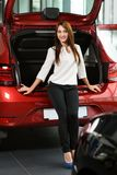 Beautiful girl is sitting on the car trunk. royalty free stock photo