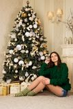 Beautiful girl sitting on the carpet near the Christmas tree Royalty Free Stock Image